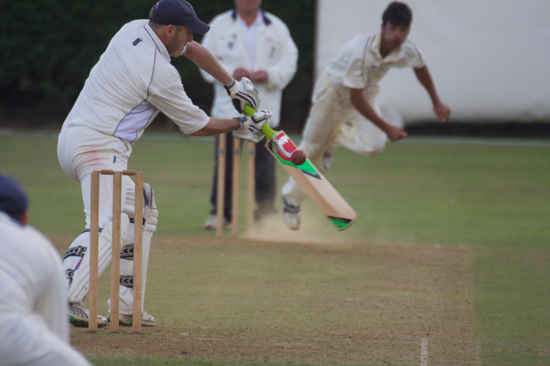 club cricket bowler beats the bat
