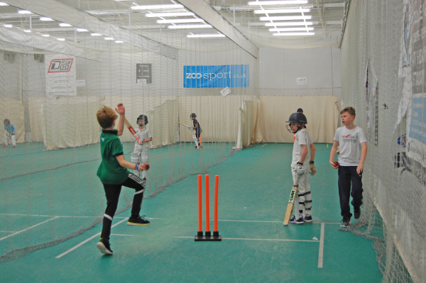junior cricket nets with a young lad bowling as the batsman watches at the non-strikers end
