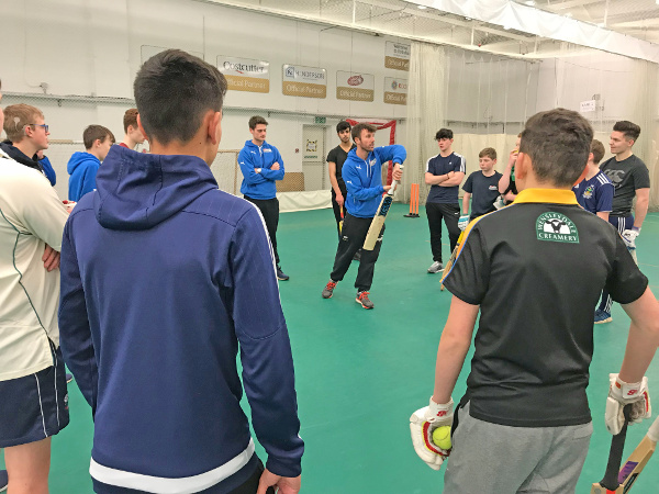 mark lawson (procoach) demonstrates a forward strike with a semi circle of young cricketers watchinbg