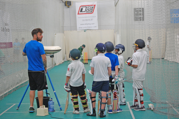 Mark Lawson of ProCoach talks to junior cricketers all padded up next to a bowling machine in a net