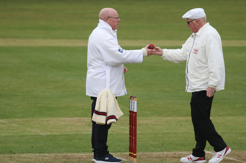 Cricket umpires exchange the cricket ball