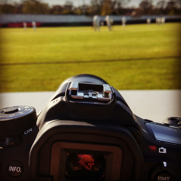 digital camera on a table at a cricket match (with the out of focus cricket going on in the background)