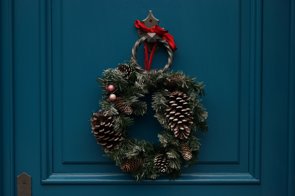 christmas wreath hangs on a navy blue door