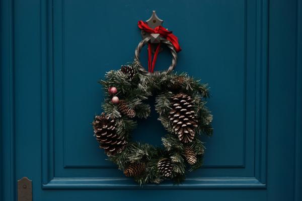 christmas wreath hangs on a navy blue door