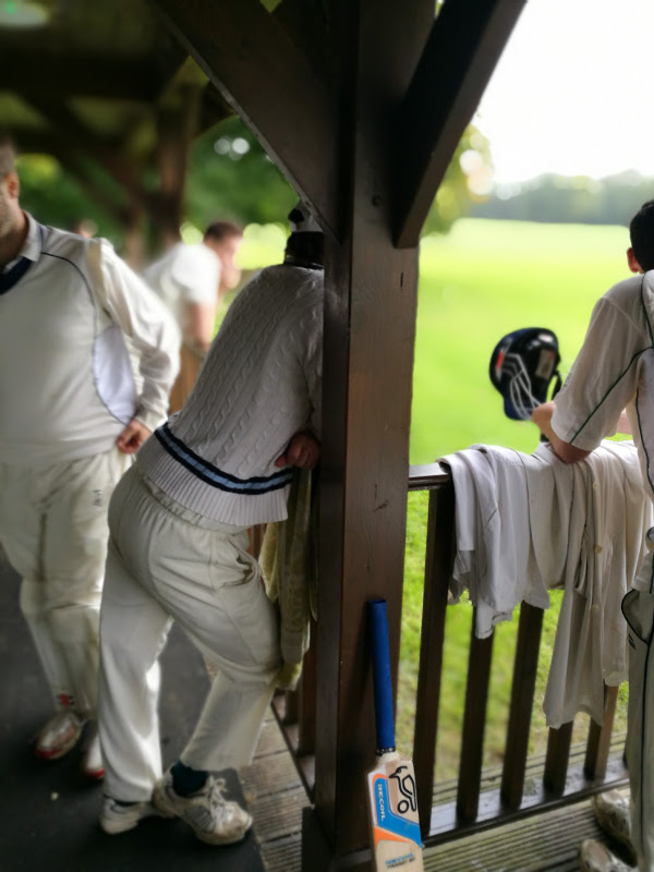 cricket club pavilion, players rest on the wooden rail outside