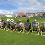 fans sit in deckchairs at scarborough cricket club