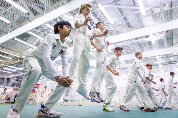 junior cricketers in whites train indoor, photo taken from floor angle looking up as they do jumps