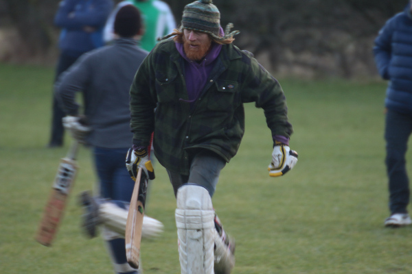 man runs between the wickets in jacket and wooley hat during a cricket match in the yorkshire dales