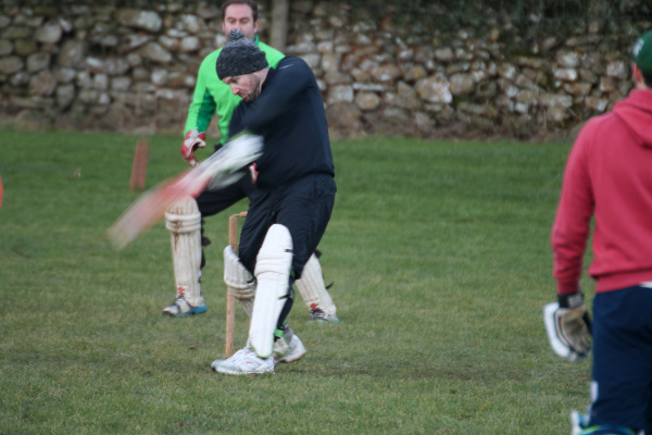 batsman in black tracksuit and hat hits out in the Yorkshire Dales cricket match