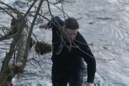 man wades through a river to fetch a cricket ball, the fast flowing water up to his waist