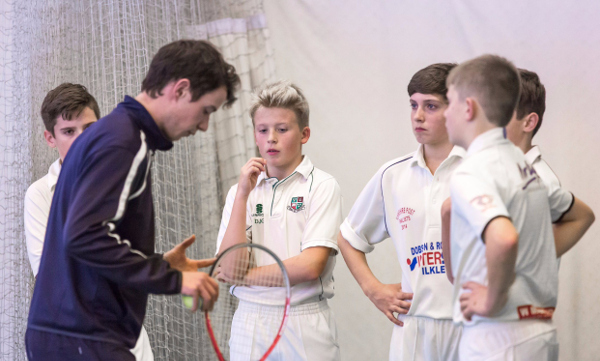 a cricket coach in blue tracksuit talks to a semi-circle of five boys at indoor cricket nets