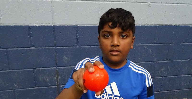 boy shows cricket ball grip with orange wind ball