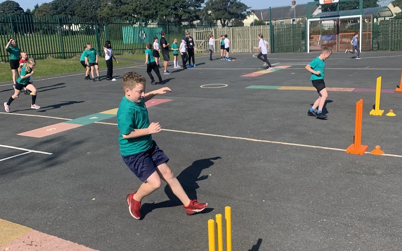 schoolchildren play cricket in the playground