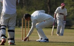 bowler picks up hand sanitiser behind the stumps in a game
